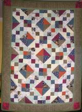 Mój pierwszy scrap quilt (Kasztanki). Początkowo mi się nie podobał, zyskał dopiero po dodaniu szerokiej bordiury. Zastąpił polarowy pled.